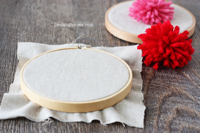 Add a pom pom to fabric in an embroidery hoop for some embroidery hoop art fun