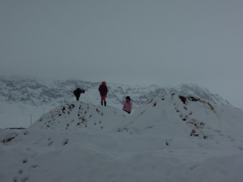 Kids playing on snow covered gravel hills.