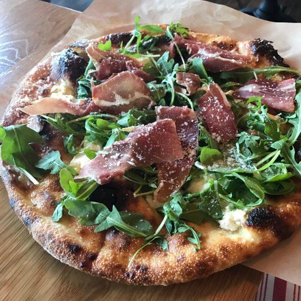 Brezza Cucina's bianca pizza with prosciutto, garlic confit, ricotta, and arugula