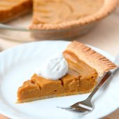 slice of pumpkin pie on a white plate with full pie in the background on wooden table