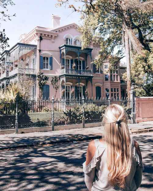 Blonde woman looking at a pink house in Garden District in New Orleans, Louisiana
