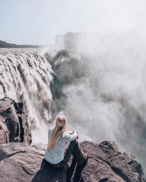 Woman looking at Dettifoss waterfall in Iceland from the edge of the cliff into the canyon. Find the top 5 waterfalls in Iceland that you don't want to miss on a Ring Road road trip.