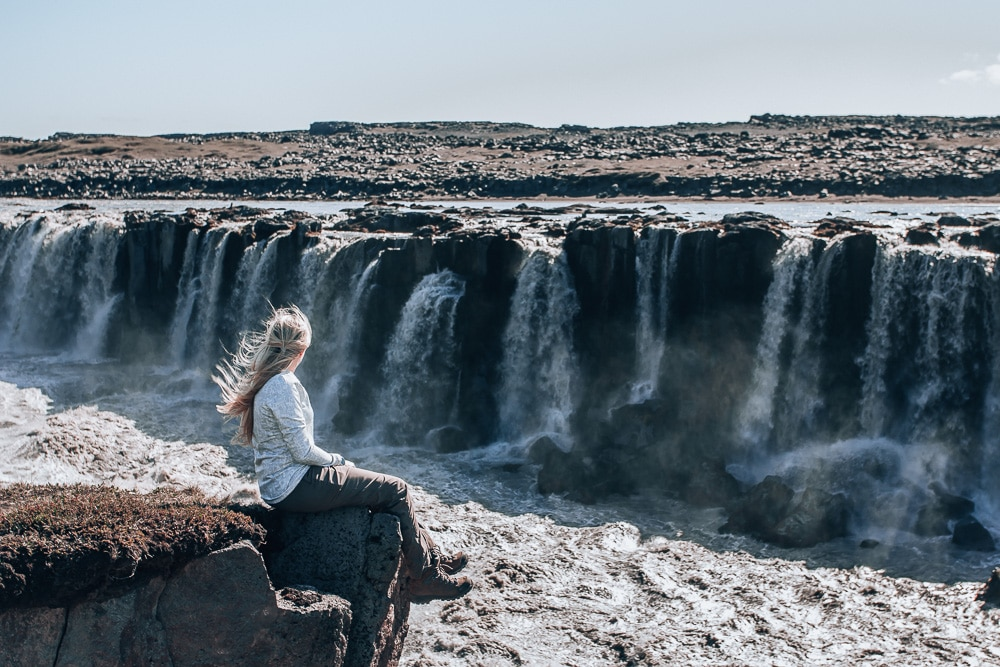 Sitting on the edge of the canyon looking at Selfoss Waterfall in Northern Iceland. Find the top 5 waterfalls in Iceland that you don't want to miss on a Ring Road road trip.