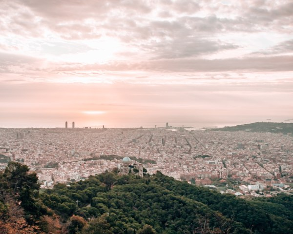 The view of the city of Barcelona from Mount Tibidabo at sunrise. Click here to find the best views and photo spots in Barcelona and an itinerary to see them all in 3 days.