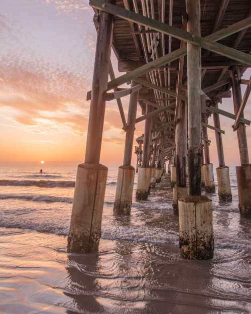 Westgate Cocoa Beach Pier at sunrise with a surfer waiting for the perfect wave. Get the scoop on the perfect Florida beach vacation in Cocoa Beach, Florida.