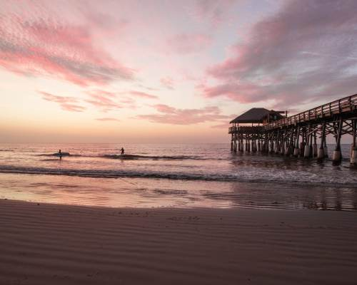 Two surfers catch waves next to the Westgate Cocoa Beach Pier. Taking surf lessons is one way to have a fun Florida beach vacation - find out more here!