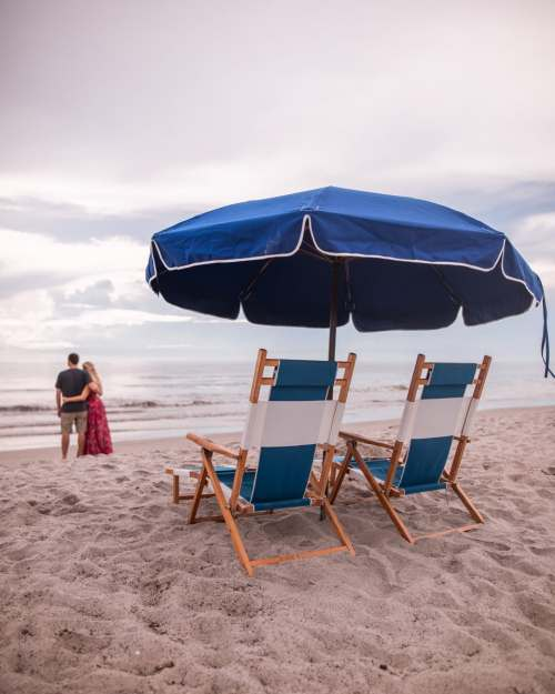 Watching the sunrise by the beach concierge umbrellas and lounge chairs at Cocoa Beach's Westgate Cocoa Beach Resort in Florida. Get a full review of the resort and all that it has to offer here.