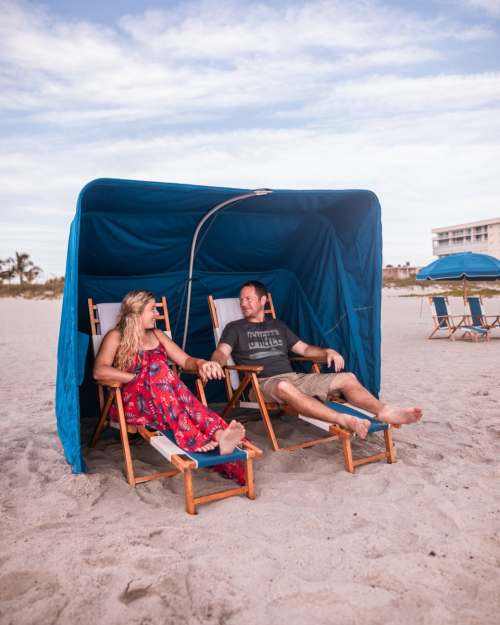 A couple relaxes in a beach cabana on Cocoa Beach at Westgate Cocoa Beach Resort in Florida. Get a full breakdown of this resort and the services it offers for a perfect Florida beach vacation here.