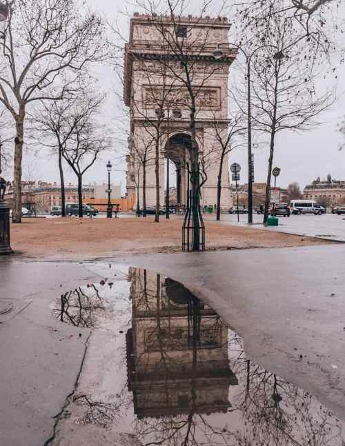A reflection photo of the Arc de Triomphe in a puddle. Find travel tips for winter in Paris in this guide to New Year's in Paris.