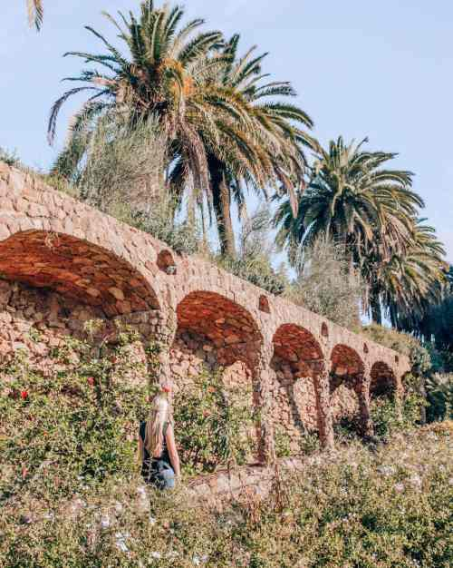 A woman walking through the Austria Gardens in Park Guell