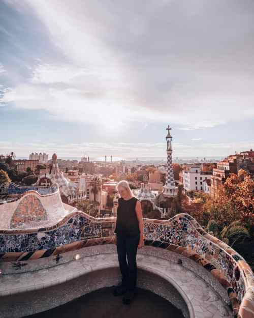 A woman stands in the Greek Theater or Nature Square in Park Guell Barcelona. Free entry gets you in before the crowds.