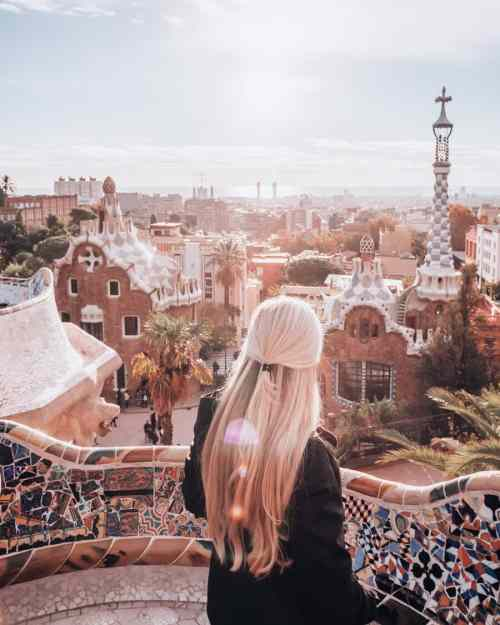 A woman poses in Park Guell Barcelona at sunrise in the Greek Theater.