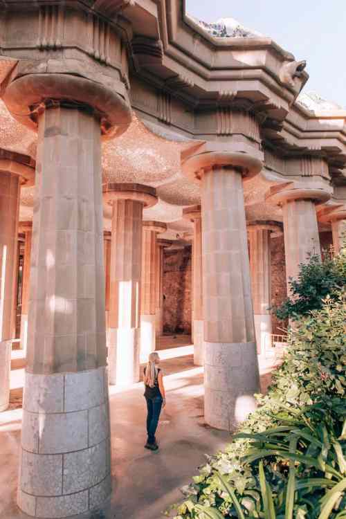 A woman standing in the Hypostyle Room in Park Guell surrounded by columns