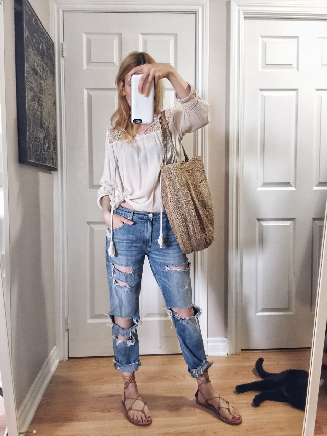 I am wearing a peasant top, boyfriend jeans, Madewell Boardwalk sandals, and a large woven circle purse