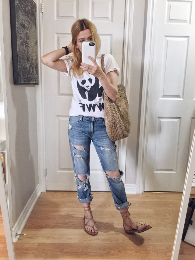 I am wearing a World Wildlife Fund T-shirt, boyfriend jeans, a large woven circle purse, and Madewell Boardwalk Sandals.