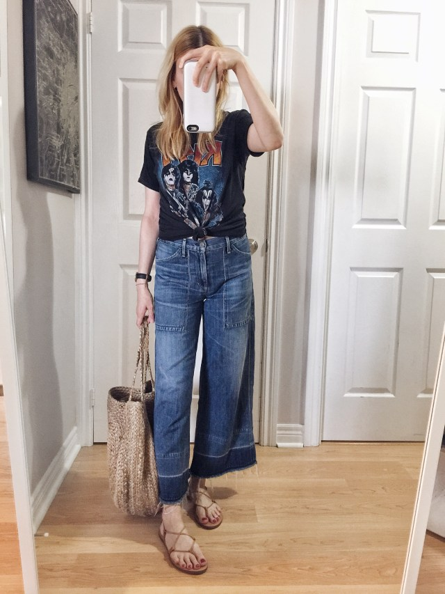 I am wearing a vintage Kiss T-shirt, wide leg jeans, a large woven circle purse, and Madewell Boardwalk Sandals.