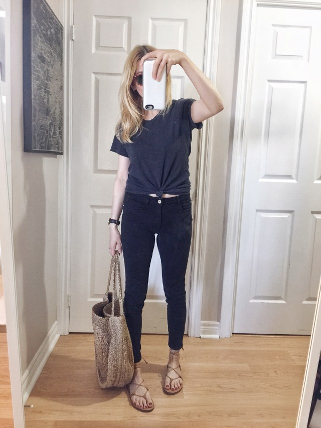 I am wearing a basic black tee knitted, black jeans, Madewell Boardwalk sandals, and a large woven circle bag.