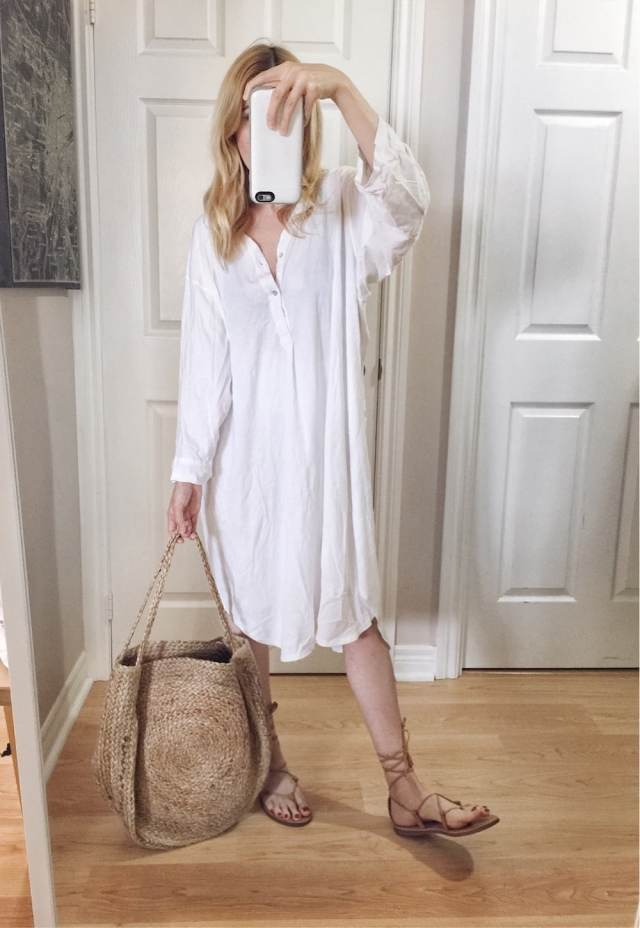 I am wearing an oversized white shirt dress, Madewell Boardwalk sandals, and a large woven circle bag.