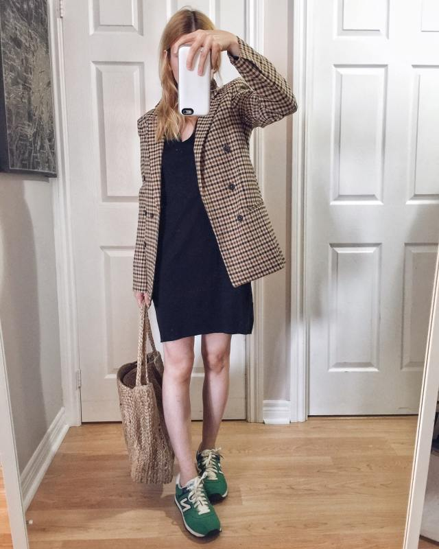 I am wearing a T-shirt dress, oversized blazer, a large woven circle purse, and green New Balance sneakers.