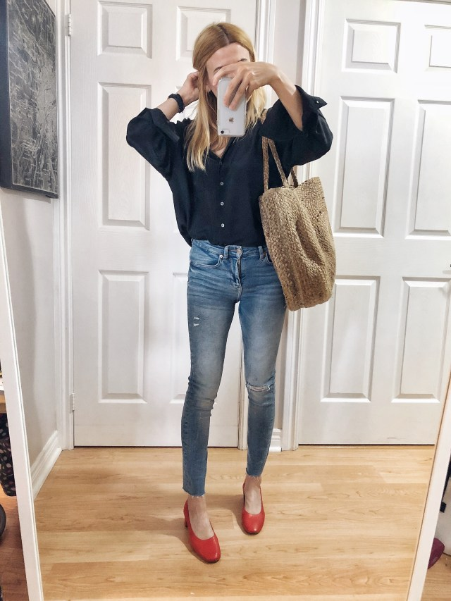 I am wearing a black silk blouse, super skinny jeans, a woven tote, and red Everlane Day Heels.