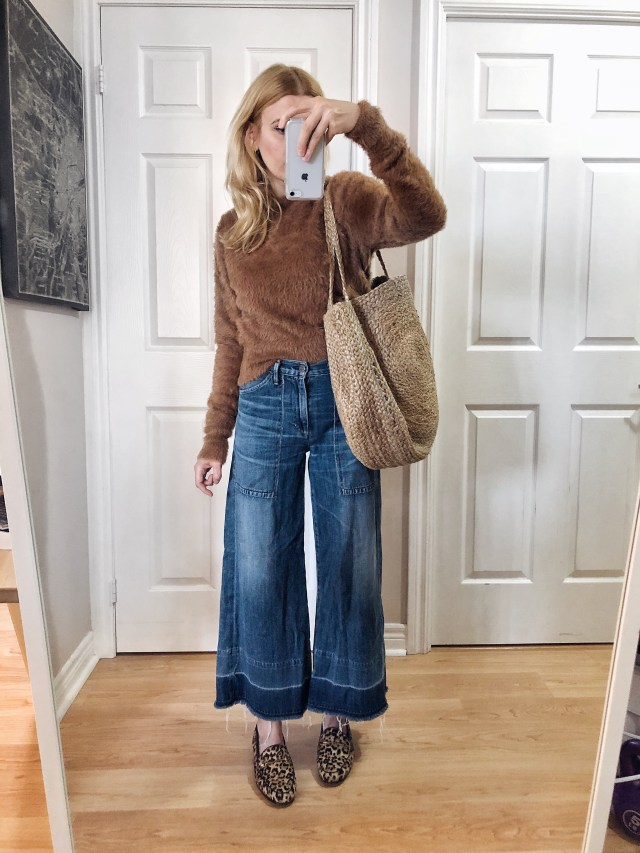 I am wearing a brown fuzzy sweater, wide leg cropped jeans, animal print loafers, and a large woven tote.