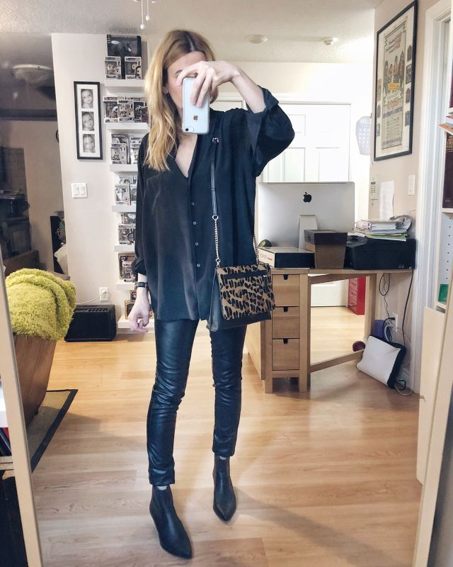 I am wearing an oversized black silk blouse, faux leather pants, Steve Madden black booties, and an animal print crossbody bag.