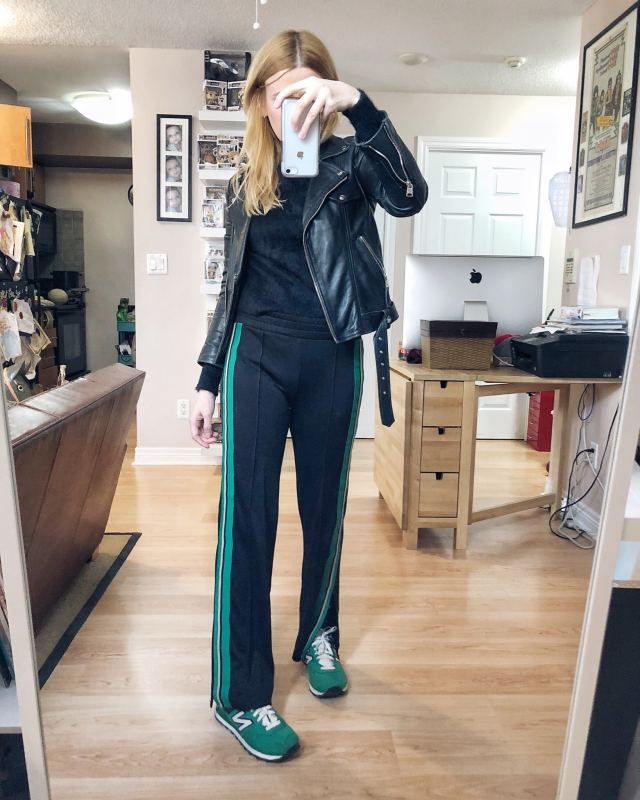 What I wore. I am wearing casual trousers with a green side stripe, a black fuzzy sweater, a moto jacket, and vintage green New Balance Sneakers. #livelovesara