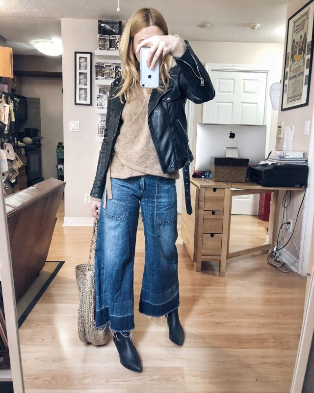 What I wore. I am wearing wide leg cropped jeans, a brown sweater, a moto jacket, and black booties with a large woven tote bag. #livelovesara