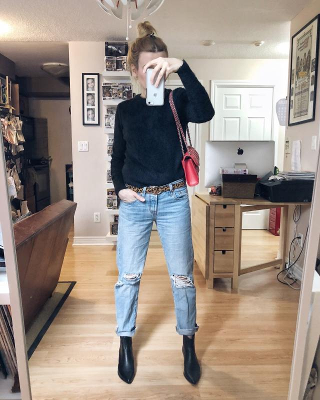 A women wearing a black Sweater, Levi's 502 jeans, black booties, and a red purse.
