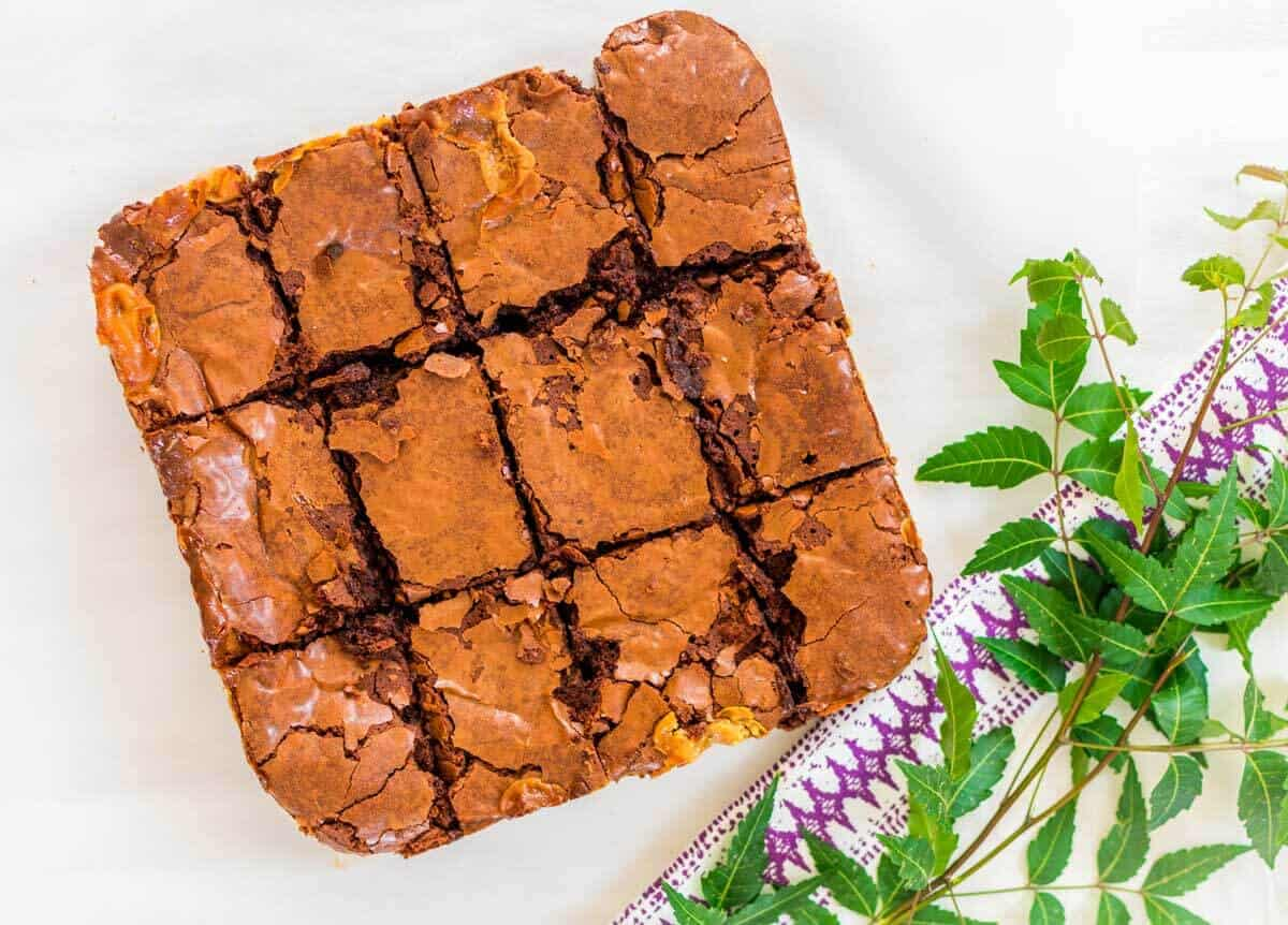 Flat lay of the fudge brownie with a cracked top and some green leaves and a purple and white towel on the side.