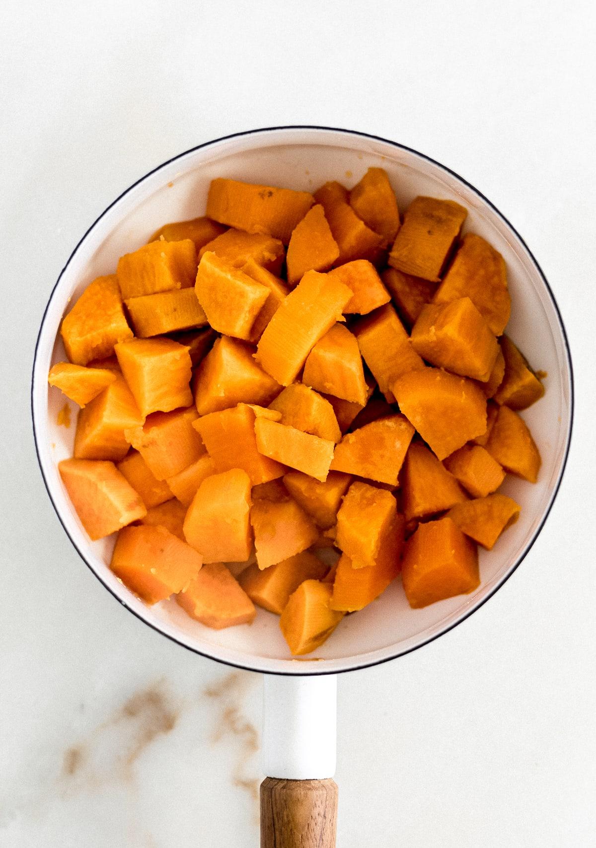 boiled, drained sweet potato cubes in a white saucepan.
