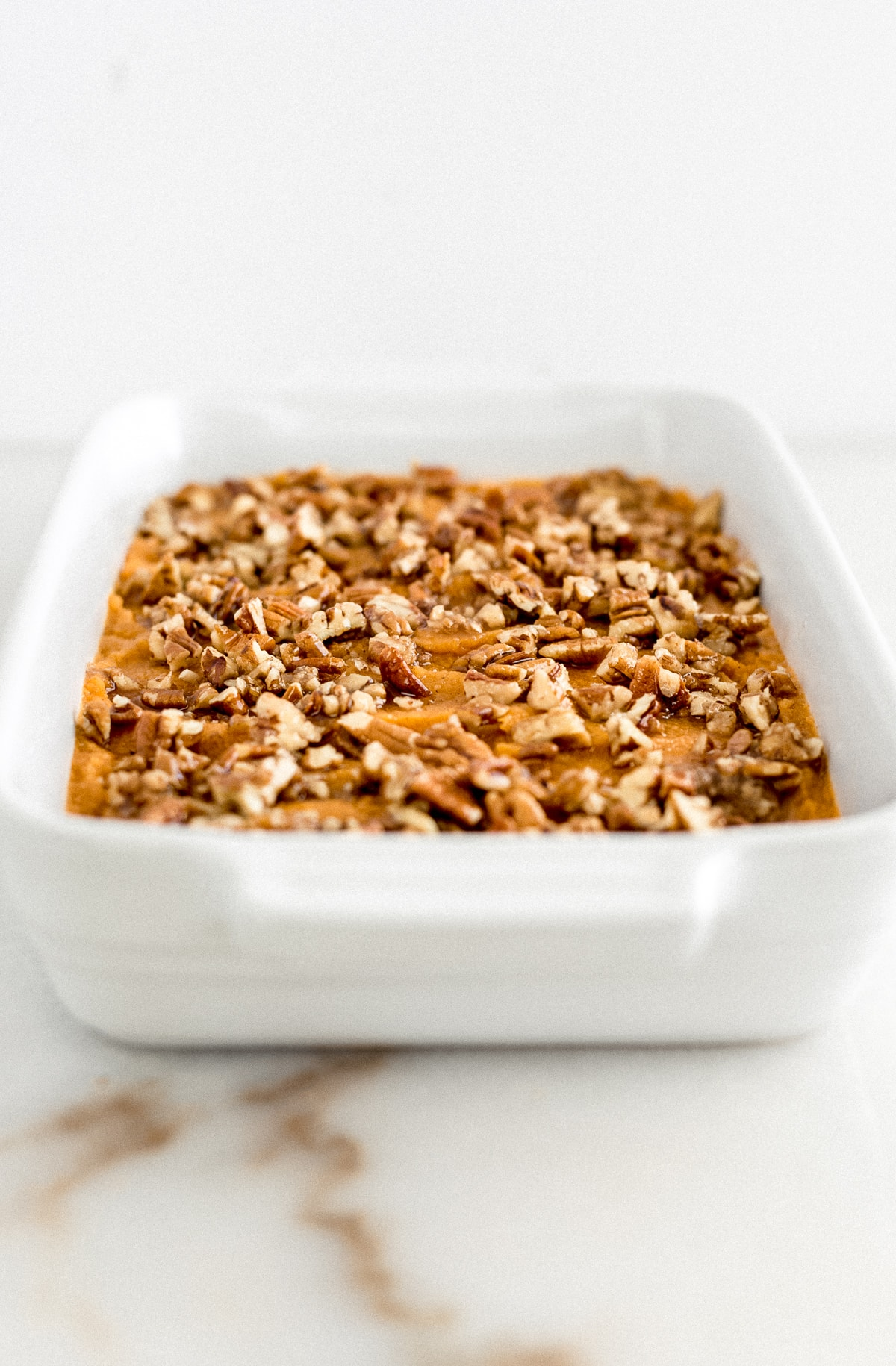 sweet potato casserole with pecan topping in a white dish before baking.