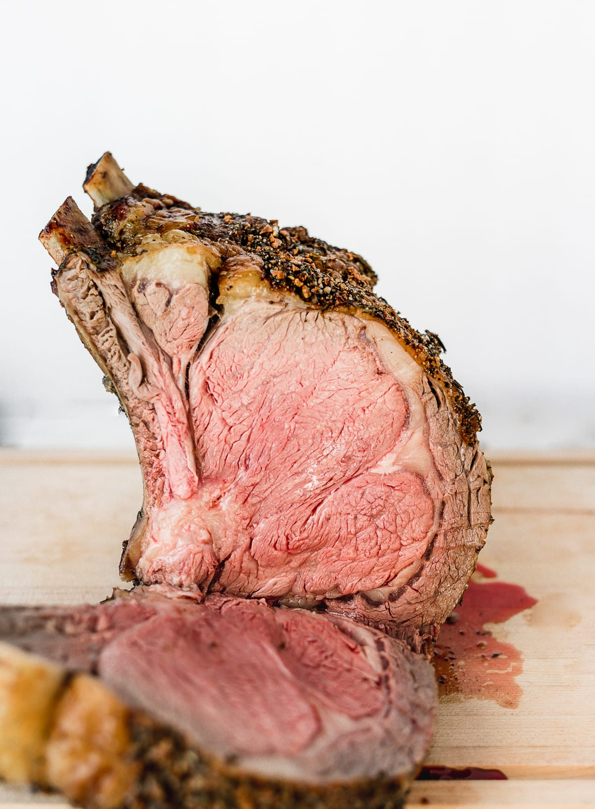 prime rib roast with a piece carved away on a cutting board.