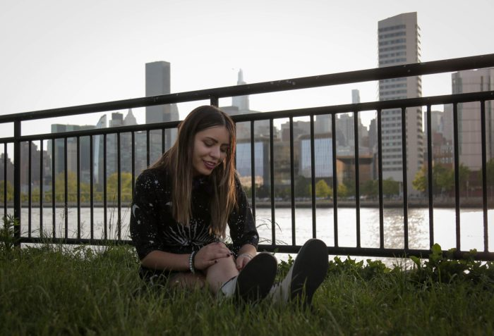 Girl Sitting in the Grass by the river thinking about Live Mic Records Services