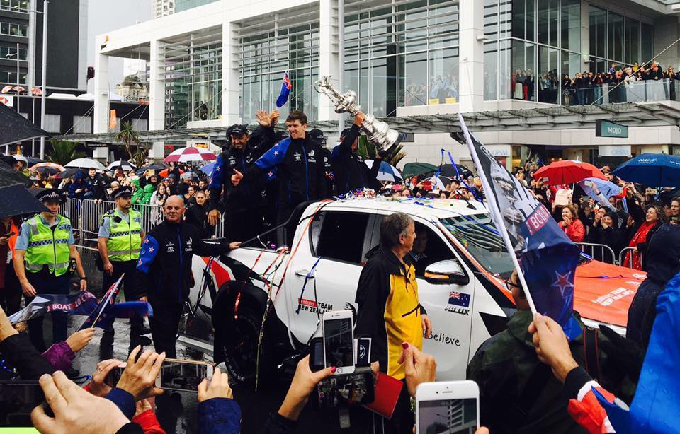 Peter Burling holds the America's Cup at the parade in Auckland.