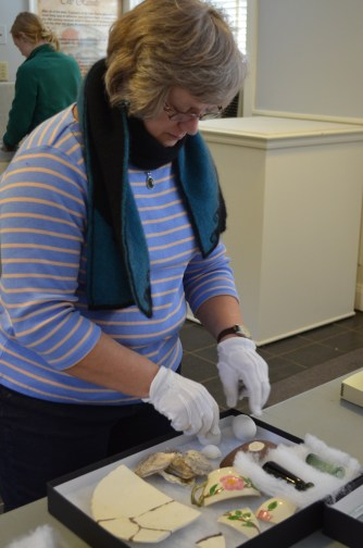 Archaeology and curatorial staff prepare objects to be moved from their temproary display case into the new exhibit area.