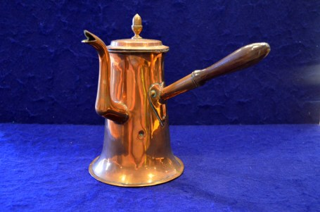 """This cooper chocolate pot features a wooden handle, """"Goose neck"""" spout with split tip, a hinged lid with inverted acorn-shaped knob, and a tinned interior."""