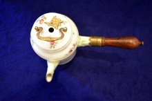 The lid has circular hole in center for the chocolate mill, a hinged brass cover cast in a floral design, and a brass pull-type handle on top of the lid.
