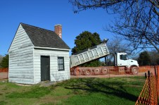 "A dump truck passes the 19th century building mistaken for George Washington's ""Surveyor's Shed"" as it lays gravel for an access road to the construction site."