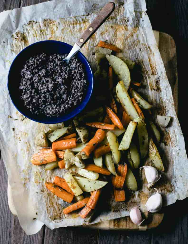 Oven roasted root vegetables and black lentils on a cutting board