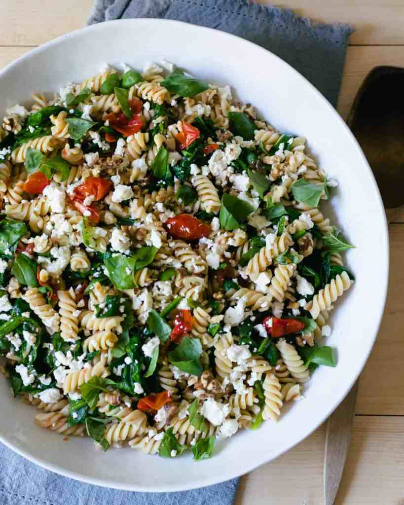pasta in a bowl with spinach and tomatoes
