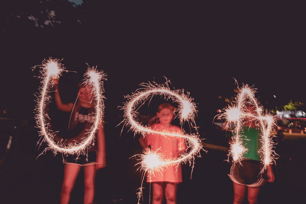 Girls spelling USA with sparklers in the night
