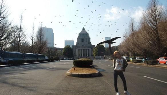 Fotografi som visar en person som står mitt i en gata. På himlen svävar kråkor. Det är ett performance som utspelar sig.