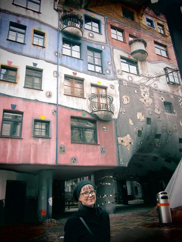 Fotografi som visar fasaden på färgglada Hundertwasserhaus i Wien. Karolina syns i halvfigur i bildens nedre del.