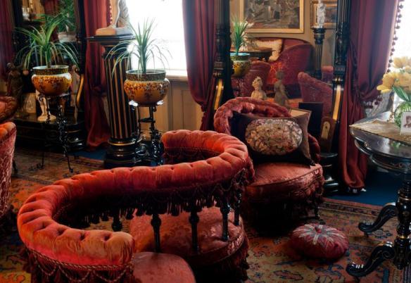 Fotografi som visar en salong mes toppade möbler och en s-formad soffa.