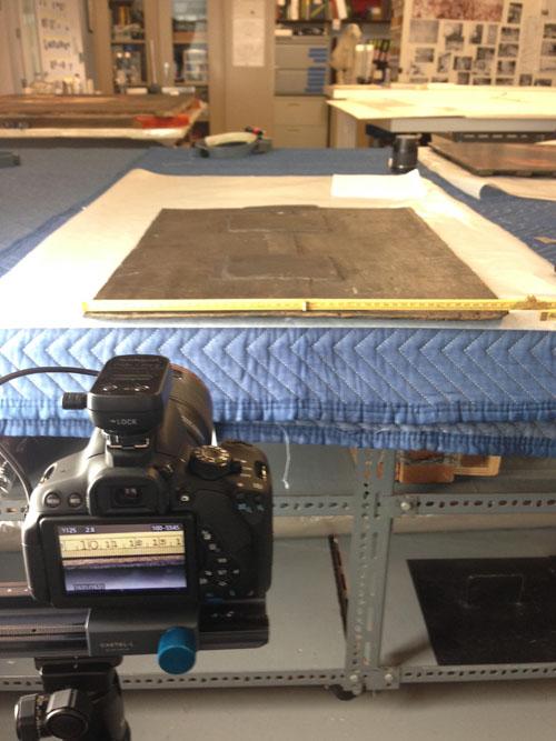 Fotografi som visar en kamera på stativ i förgrunden. Kameran är riktad mot ett bord där en träpanel ligger.