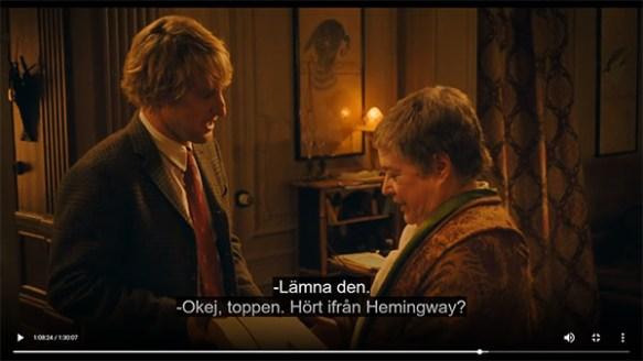 Två personer, en man och en äldre kvinna, står mitt emot varandra och tycks samtala i ett dovt upplyst rum. Ur filmen Midnatt i Paris.