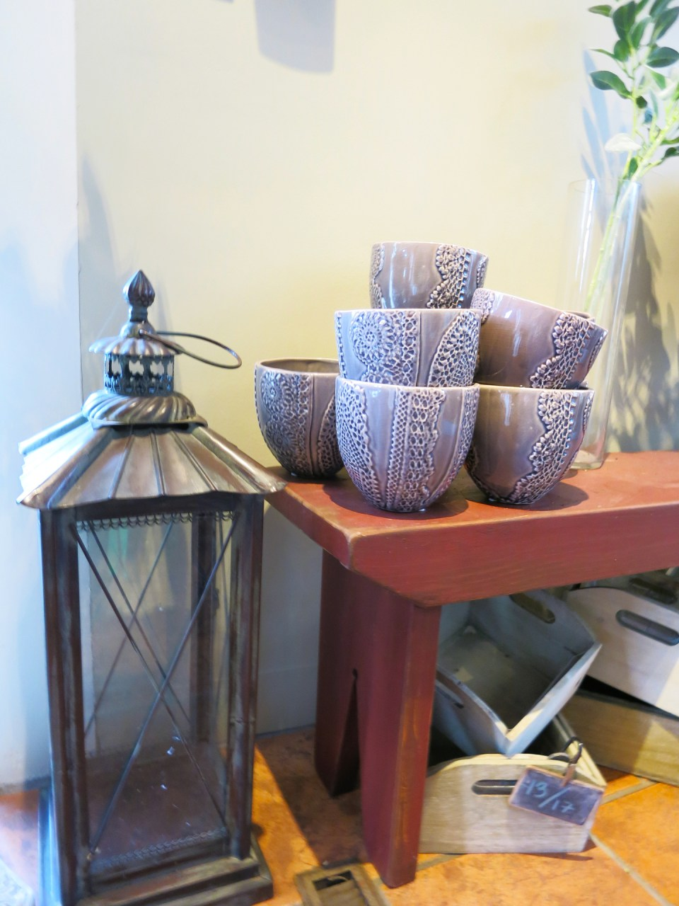 Purple bowls on a red bench and a metal lantern on display in Studio 539 located on Wickenden Street in Providence, RI