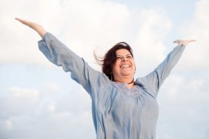 Energetic mature hispanic woman enjoying life on the beach