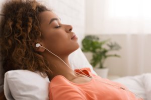 African-american woman listening calm music and relaxing, lying in bed